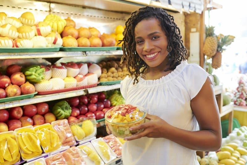 Jolie femme avec le bol de salade de fruits photographie stock