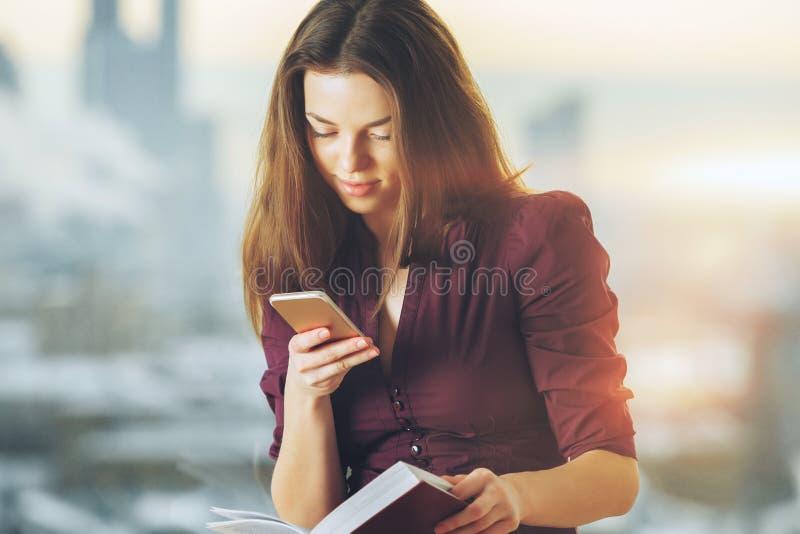Jolie femme avec le smartphone et le livre photos stock