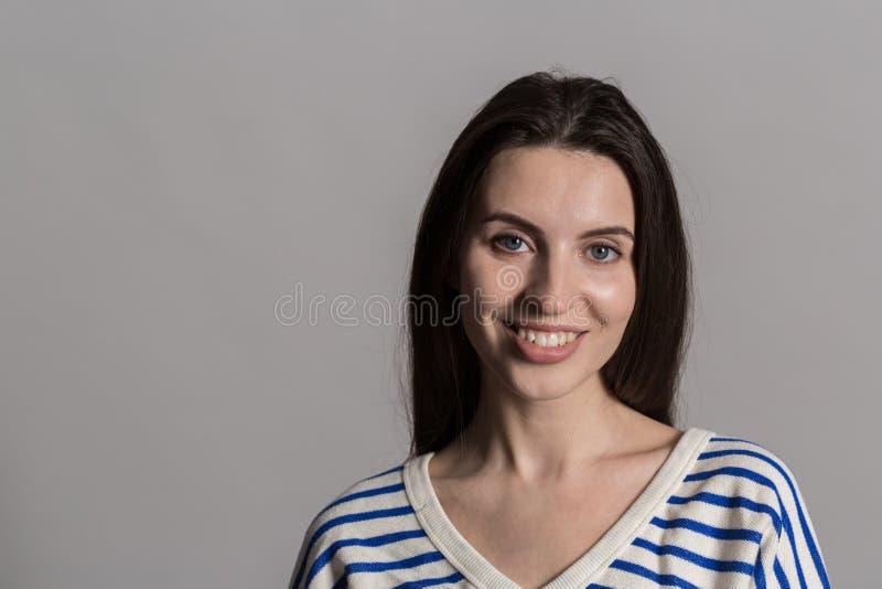Jolie femme avec les cheveux pelucheux, habillés en passant contre un mur gris de studio photographie stock