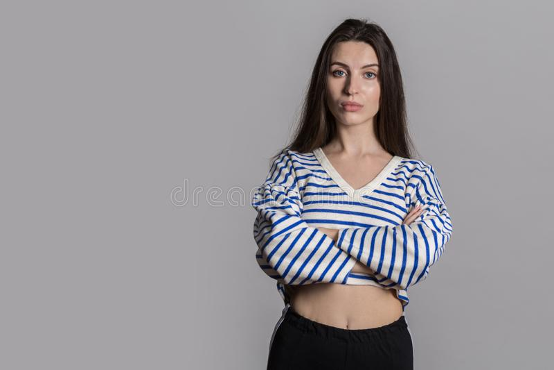Jolie femme avec les cheveux pelucheux, habillés en passant contre un mur gris de studio photo libre de droits
