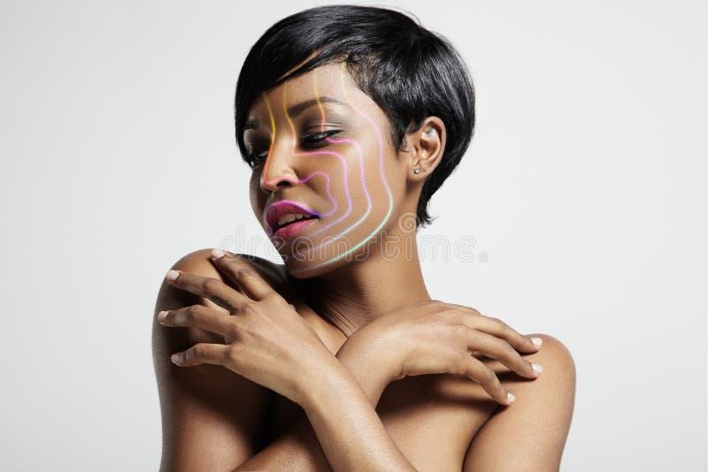Jolie femme avec les discriminations raciales d'un arc-en-ciel sur son visage photos stock