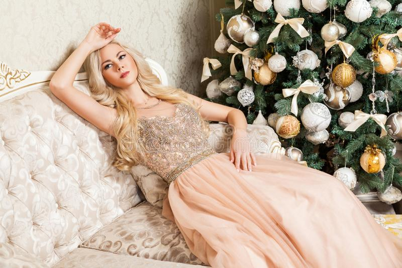 Jolie femme blonde dans la pose se reposante gonflée de robe de soirée de belles vacances sur le sofa près de l'arbre de Noël ten images stock