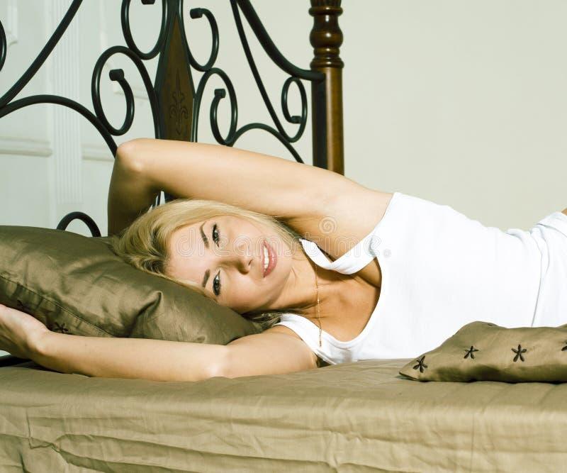 Jolie femme blonde s'étendant dans le lit, lingerie sensuelle rêvant le sourire heureux photographie stock