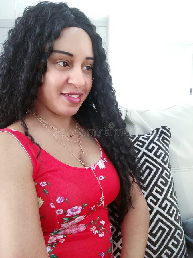 Jolie femme bouclée de cheveux noirs dans la vue de côté de robe rouge de fleur photo libre de droits