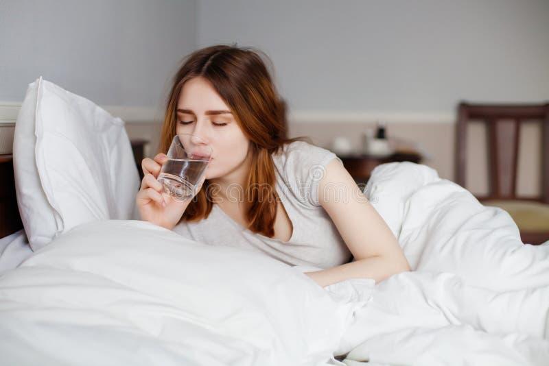 Jolie femme calme buvant une eau en verre dans la chambre à coucher lumineuse image stock