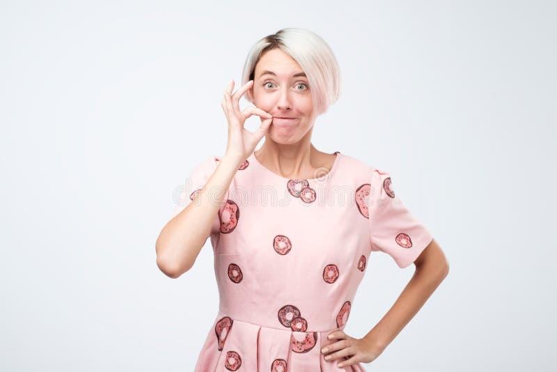Jolie femme caucasienne avec les cheveux teints courts fermant la fermeture éclair sa bouche fermée image libre de droits