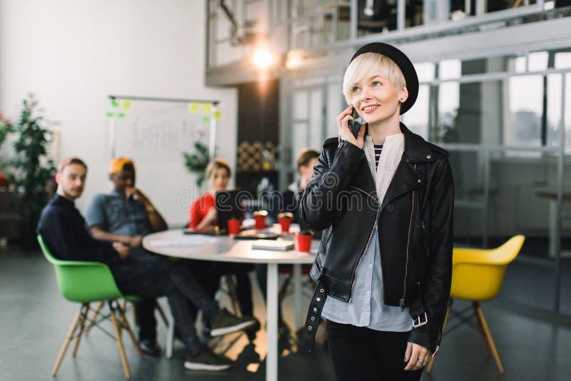 Jolie femme caucasienne d'affaires dans le chapeau et la veste utilisant le téléphone femme européenne réussie d'affaires, parlan photos stock