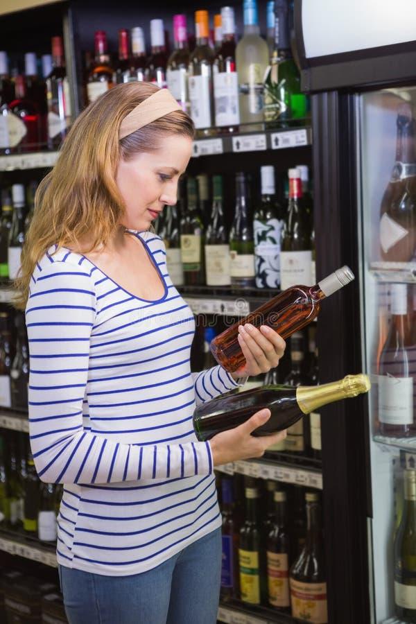 Download Jolie Femme Choisissant La Bouteille De Vin Photo stock - Image du liquor, cueillette: 56489088