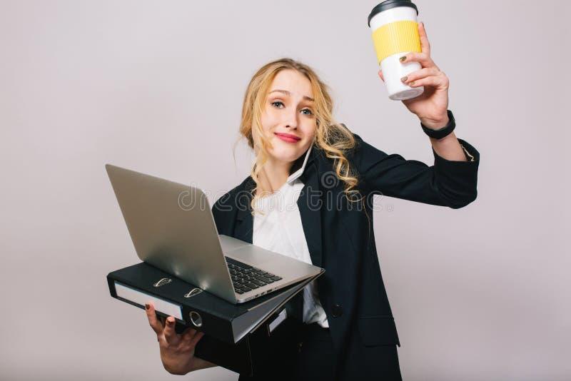 Jolie femme d'affaires blonde avec l'ordinateur portable, dossier, boîte, caffee dans des mains parlant au téléphone d'isolement  photo libre de droits