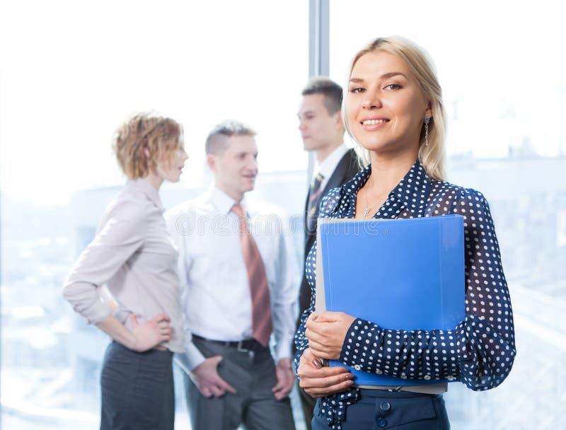 Jolie femme d'affaires dans l'appareil-photo de regard avant avec l'équipe sur le fond images libres de droits
