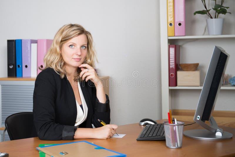 jolie femme d'affaires de sourire à l'aide de l'ordinateur portable et de l'ordinateur tout en faisant quelques écritures au bure image libre de droits