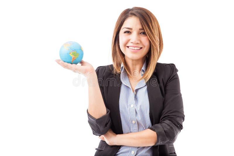 Jolie femme d'affaires hispanique avec un globe image libre de droits