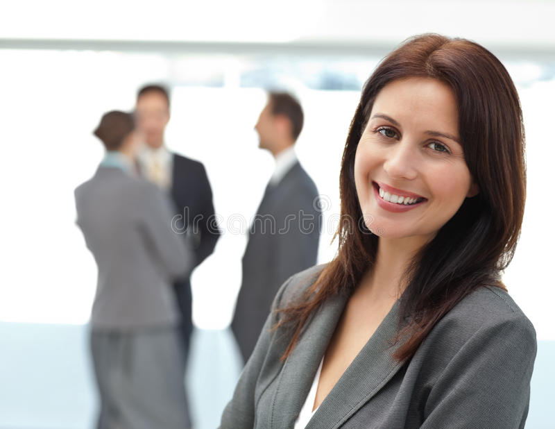 Jolie femme d'affaires posant devant son équipe image libre de droits