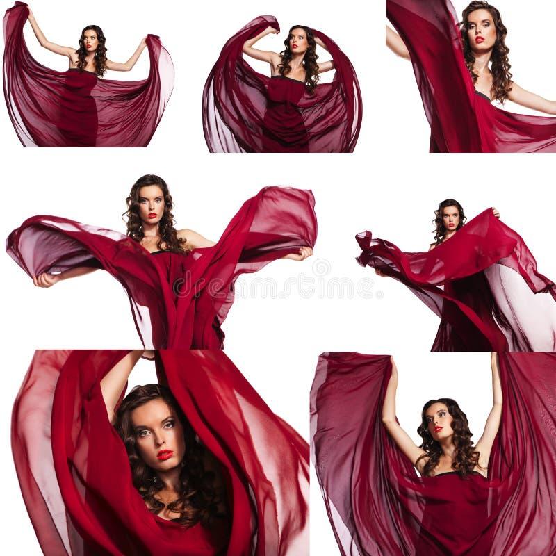 Jolie femme dans la longue robe rouge posant avec le tissu de ondulation d'isolement photographie stock