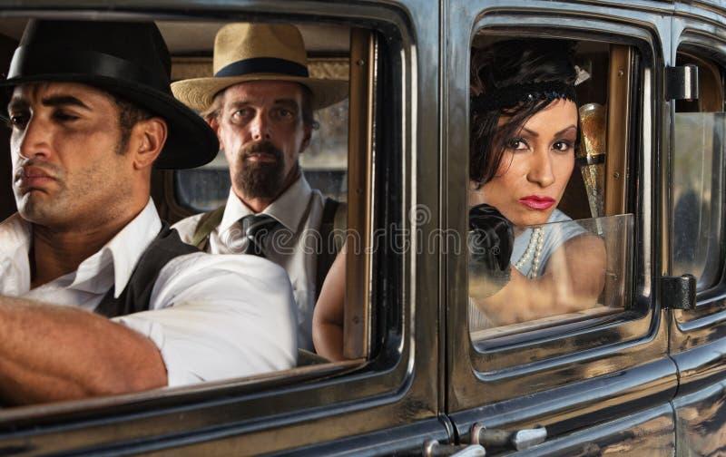 Jolie femme dans la voiture avec des bandits photos stock