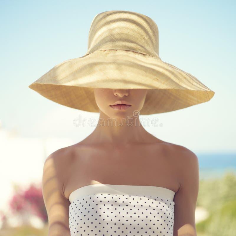 Jolie femme dans le chapeau de paille photographie stock libre de droits