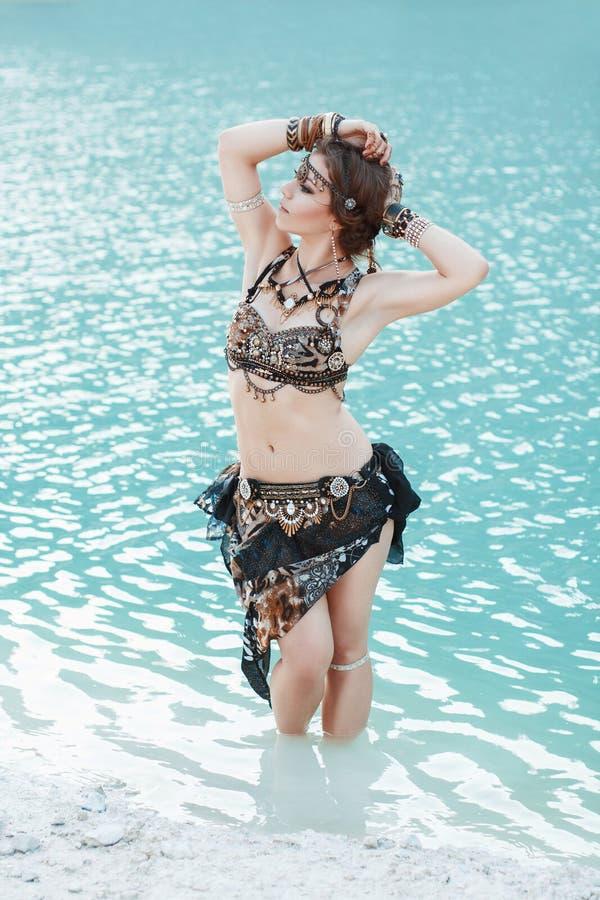 Jolie femme dans le style tribal sur la plage blanche de sable près de l'eau image stock