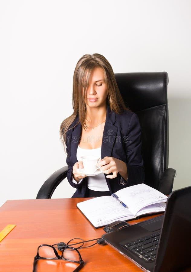 Jolie femme dans un costume se reposant à un bureau avec l'ordinateur la femme boit du café d'une tasse blanche photographie stock libre de droits