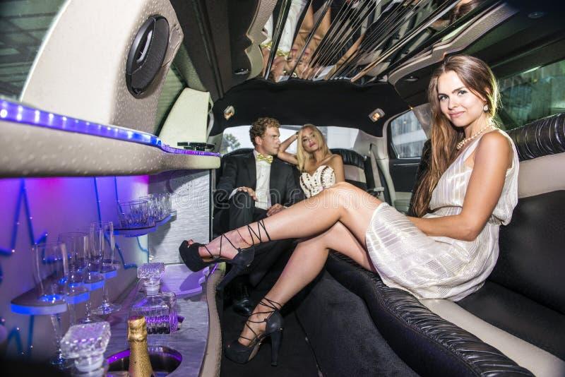 Jolie femme dans une limousine luxueuse photos stock