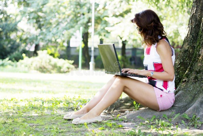 Jolie femme de brune à l'aide de l'ordinateur portable dans le parc image libre de droits