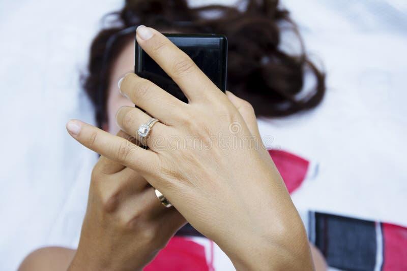 Jolie femme de brune à l'aide du smartphone dans le parc photo stock