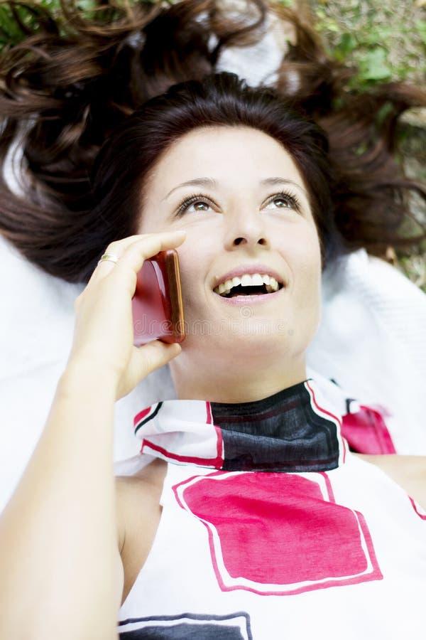 Jolie femme de brune à l'aide du smartphone dans le parc image stock