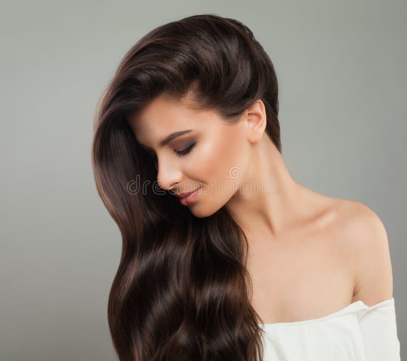 Jolie femme de brune avec la coiffure onduleuse Beau profil femelle Concept de soins capillaires image libre de droits