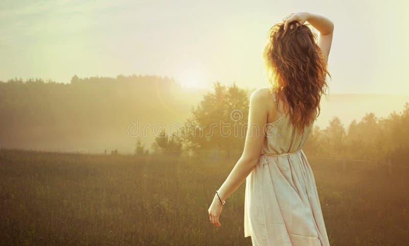 Jolie femme de brune observant le coucher du soleil photos stock