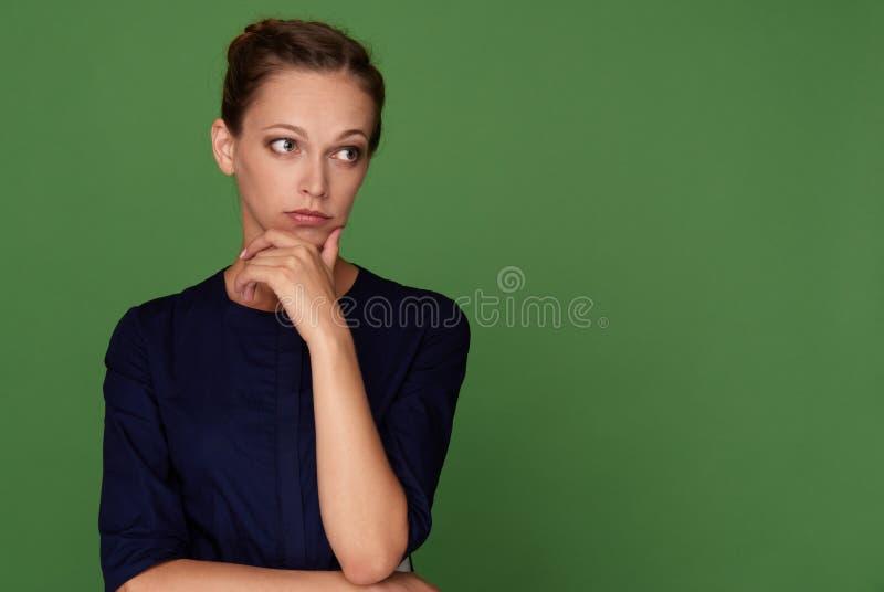 Jolie femme de brune regardant loin ayante douteux photographie stock