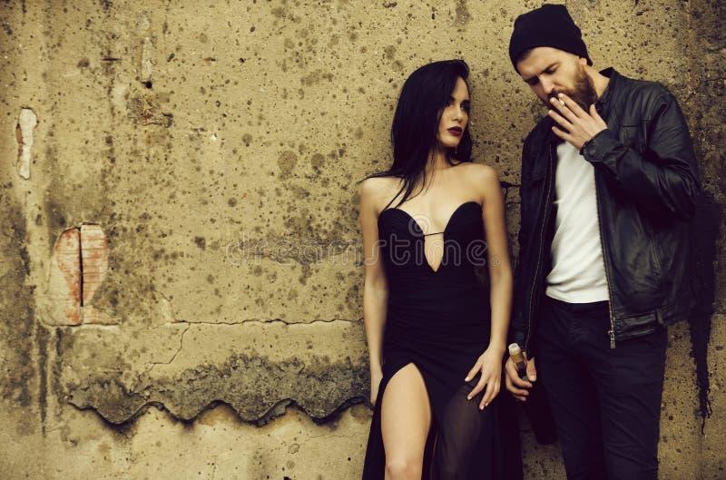Jolie femme de mode dans le tabagisme noir sexy de robe et d'homme photographie stock