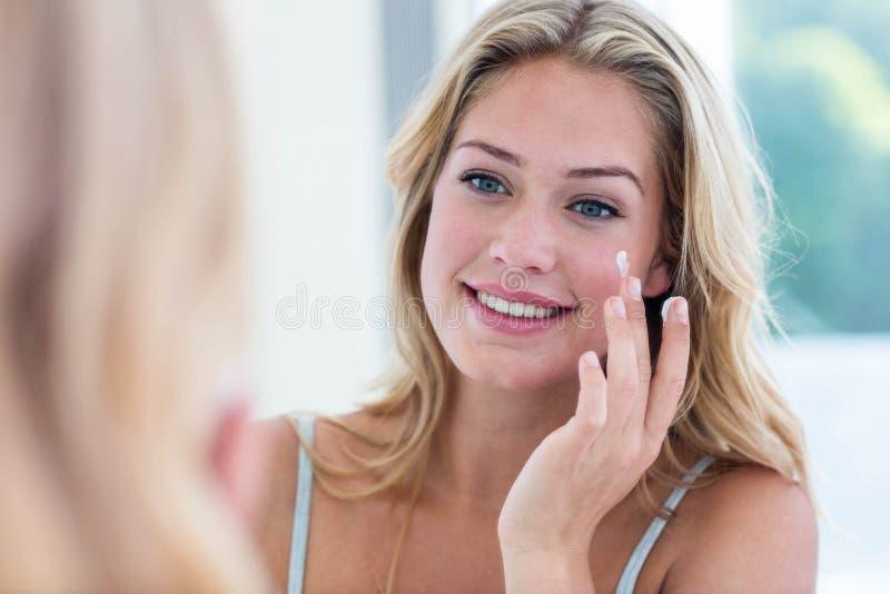 Jolie femme de sourire appliquant la crème sur son visage photo stock