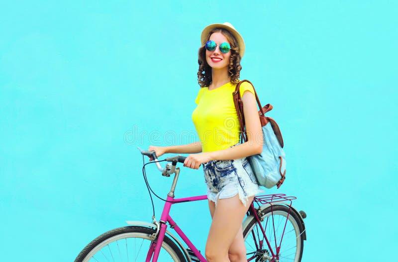 Jolie femme de sourire avec la bicyclette au-dessus du bleu coloré photo stock