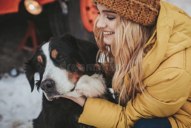 Jolie femme de sourire embrassant son chien aim? image libre de droits