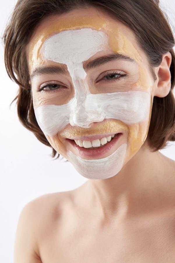 Jolie femme de sourire heureuse avec le masque protecteur images stock