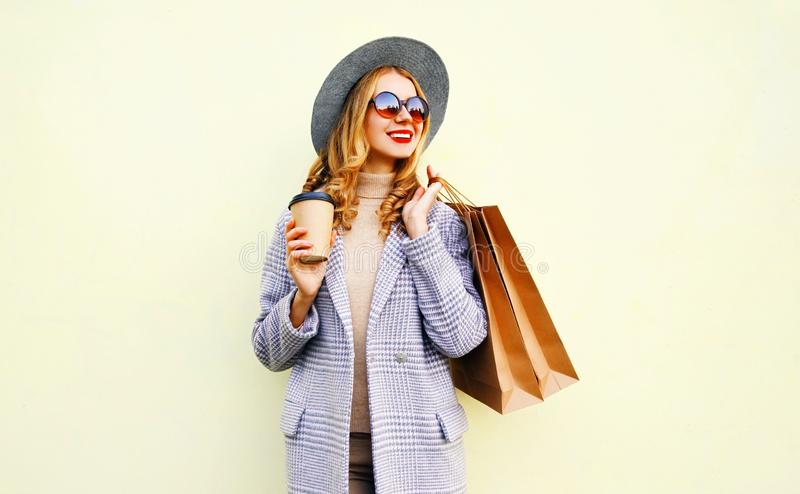 Jolie femme de sourire de portrait avec des sacs à provisions, tenant la tasse de café, manteau rose de port, chapeau rond images stock