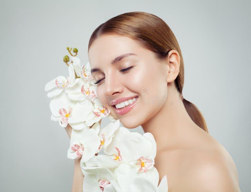 Jolie femme de station thermale avec la peau saine, le sourire mignon et la fleur d'orchidée photos libres de droits
