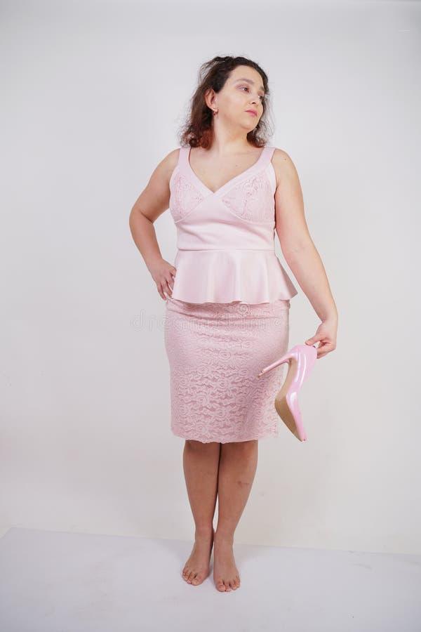 Jolie femme dodue dans la robe rose avec les talons stylets de cuir verni sur le fond blanc dans le studio image libre de droits