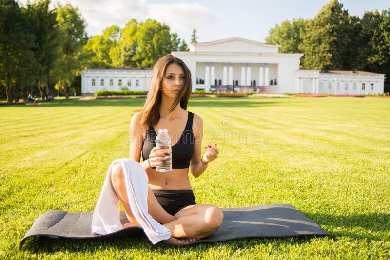 Jolie femme en bonne santé avec de l'eau la serviette et de gymnase image libre de droits