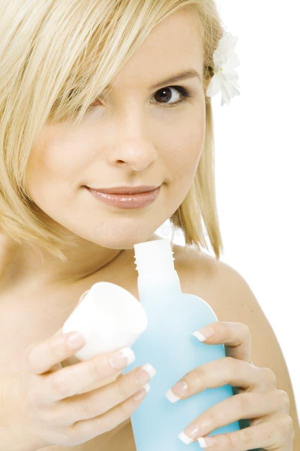 Jolie femme examinant son nouveau cosmétique image stock