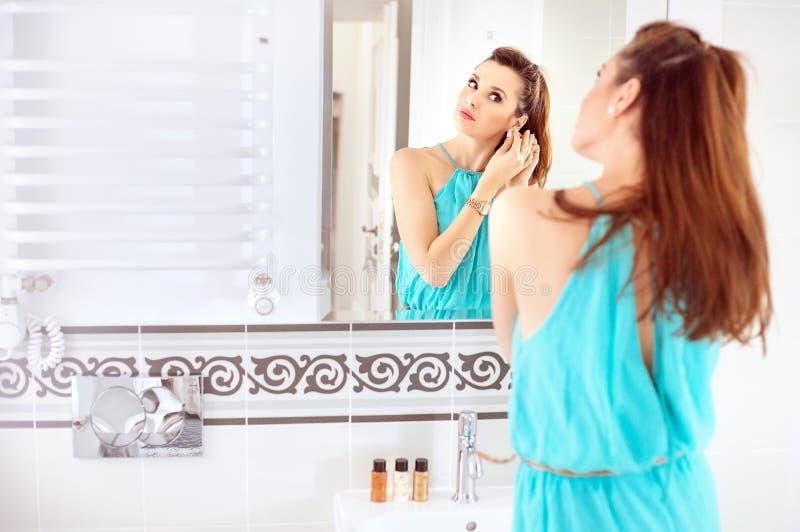 Jolie femme faisant un maquillage dans la salle de bains image stock