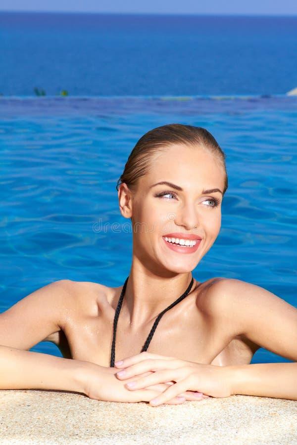 Jolie femme heureuse au bord de la piscine photo stock