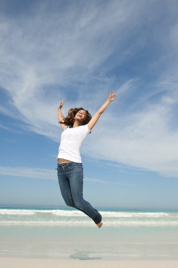 Jolie femme heureuse branchant pour la joie à la plage photo libre de droits