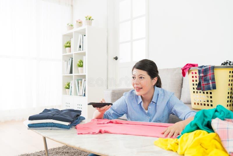Jolie femme heureuse jugeant la TV à télécommande photographie stock