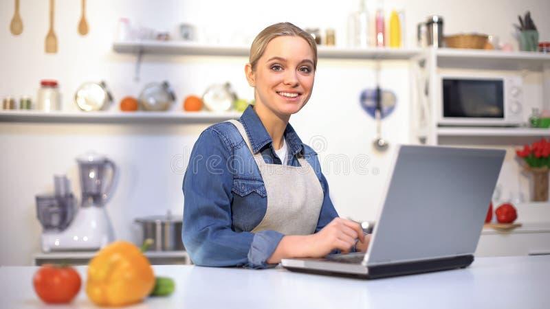 Jolie femme heureuse recherchant faisant cuire la recette dans l'Internet, utilisant l'ordinateur portable, cuisine images stock