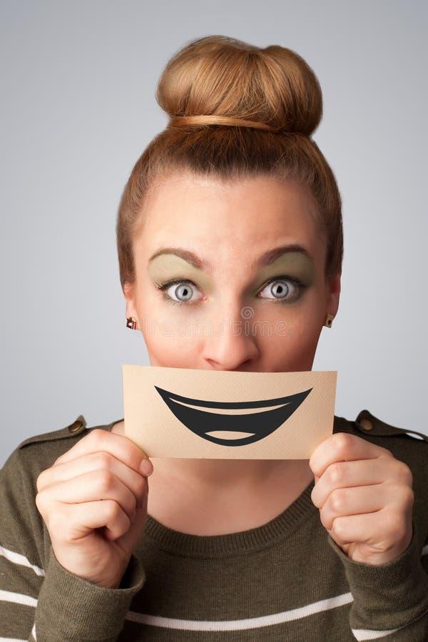 Jolie femme heureuse tenant la carte avec le smiley drôle photographie stock