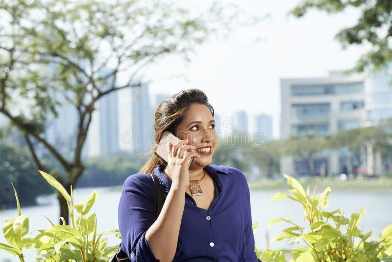Jolie femme invitant le téléphone image stock