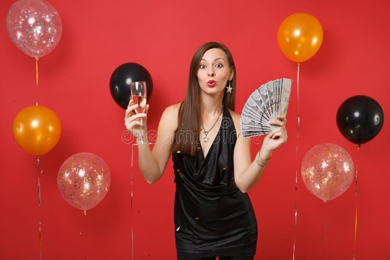 Jolie femme lèvres célébrant, de soufflement et tenant un bon nombre de paquet de dollars, argent d'argent liquide, verre de cham image stock