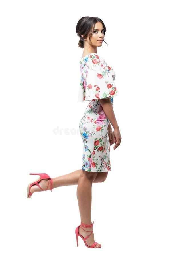 Jolie femme latine dans la robe de soirée florale posant avec la jambe augmentée  Vue de côté photo stock