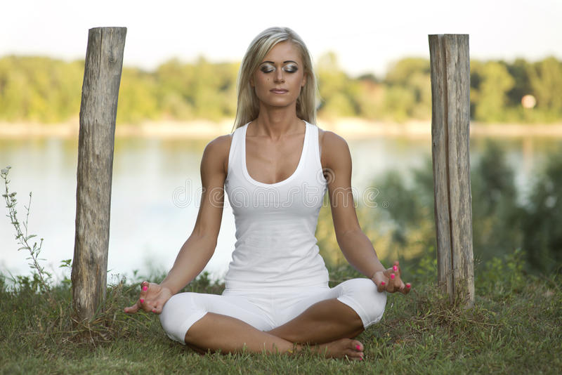 Jolie femme Lotus Pose Outdoors images stock