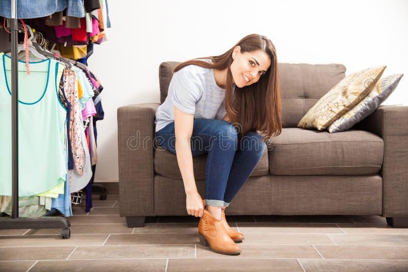 Jolie femme mettant des chaussures dessus à la maison images libres de droits
